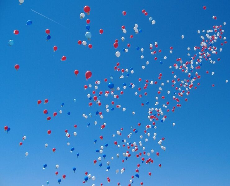Colourful helium balloons against a blue sky