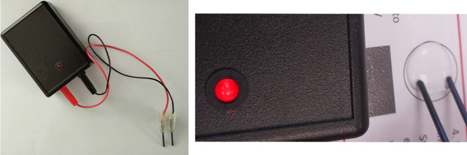 The LED of a conductivity indicator shines brightly when the electrodes touch a drop of water containing salt.