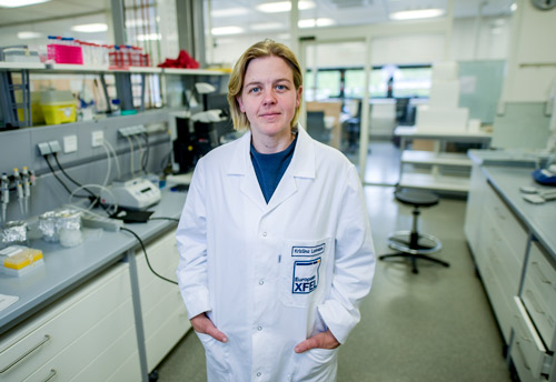 Woman in an European XFEL lab coat standing in the middle of a laboratory